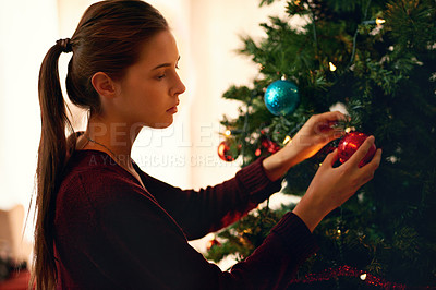 Buy stock photo Shot of an attractive young woman decorating a christmas tree