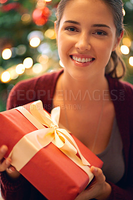 Buy stock photo Portrait of a beautiful young woman holding a present in front of a christmas tree