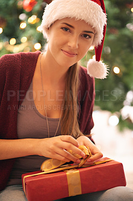 Buy stock photo Portrait of a beautiful young woman opening a present in front of a christmas tree