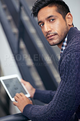 Buy stock photo A handsome businessman holding a digital tablet on a stairwell