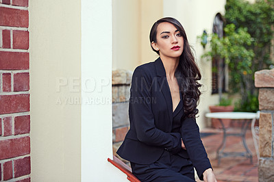 Buy stock photo Shot of a woman wearing a classic feminine suit leaning against an architectural feature