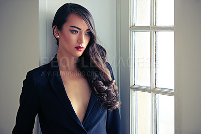 Buy stock photo Shot of a beautiful woman wearing a classic feminine suit posing alongside french doors