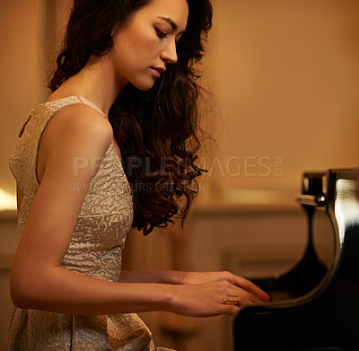 Buy stock photo Side view of a beautiful young woman playing the piano