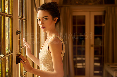 Buy stock photo Portrait of a beautiful and elegant young woman standing by a window