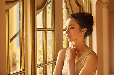 Buy stock photo Shot of a beautiful and elegant young woman standing by a window