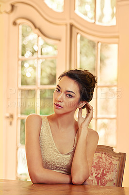 Buy stock photo Portrait of a beautiful young woman sitting at a table in her elegant home