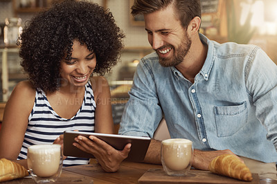 Buy stock photo Shot of a beautiful woman showing something on her digital tablet to a friend in a coffee shop