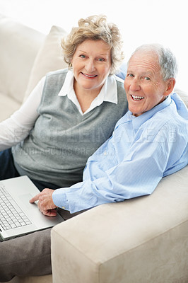 Buy stock photo Portrait of a senior couple working on their laptop at home