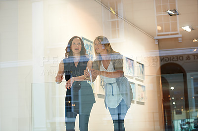 Buy stock photo Shot of a young woman looking through a window at a gallery