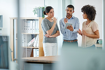 Buy stock photo Shot of office colleagues having a discussion over a digital tablet