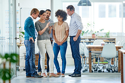 Buy stock photo Shot of a group of office colleagues having a discussion over a digital tablet