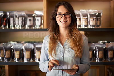 Buy stock photo Portrait of a smiling woman holding a digital tablet in a shop with shelves behind her