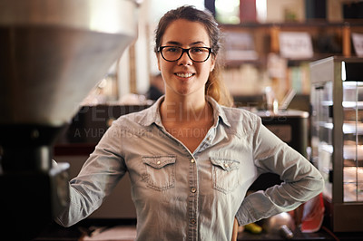 Buy stock photo Portrait of a young woman standing alongside an old-fashioned coffee roasting machine