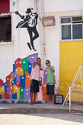 Buy stock photo Shot of two young graffiti artists standing by their wall art