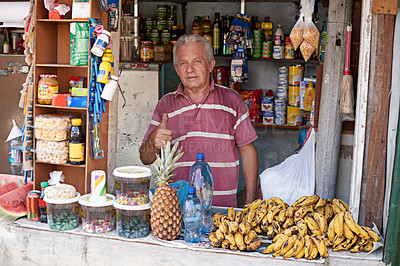 Buy stock photo Portrait of a street vendor selling a variety of food at his stall