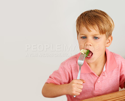 Buy stock photo A little boy very unhappy with having to eat vegetables