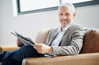 Buy stock photo Portrait of a handsome mature man relaxing with the newspaper at home