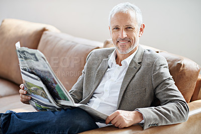 Buy stock photo Portrait of a handsome mature man relaxing with the newspaper on the sofa