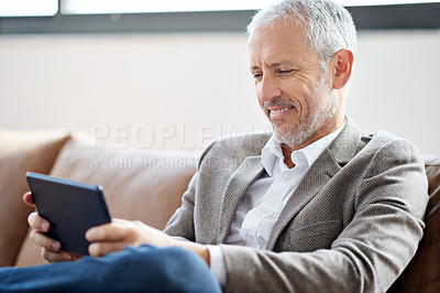 Buy stock photo Shot of a handsome mature man using his tablet while sitting on the sofa at home