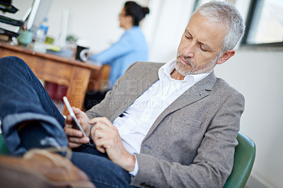 Buy stock photo Shot of a mature businessman using a cellphone while sitting in an office