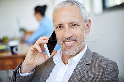 Buy stock photo Portrait of a mature businessman talking on a cellphone while sitting in an office