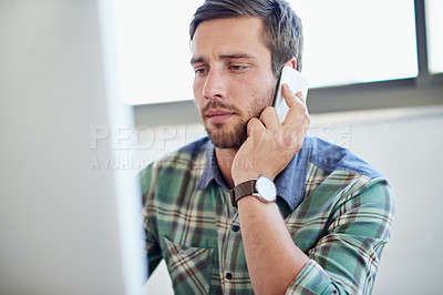 Buy stock photo Shot of a young designer talking on a cellphone while working on a computer