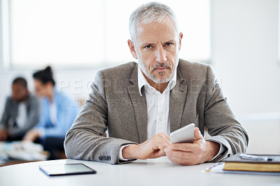 Buy stock photo Shot of a mature businessman using a cellphone while sitting at a table in an office