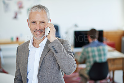 Buy stock photo Portrait of a mature businessman talking on a cellphone while standing in an office