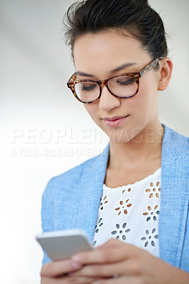 Buy stock photo Shot of an attractive young woman using a cellphone in an office