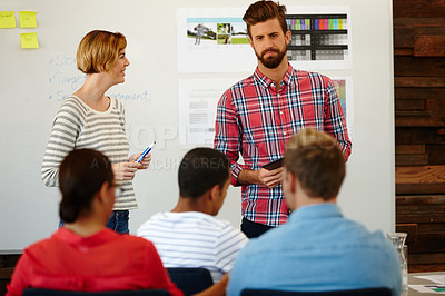 Buy stock photo Shot of a group of young designers having a brainstorming meeting at a whiteboard