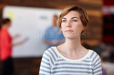 Buy stock photo A young female designer looking thoughtful while her colleagues work in the background