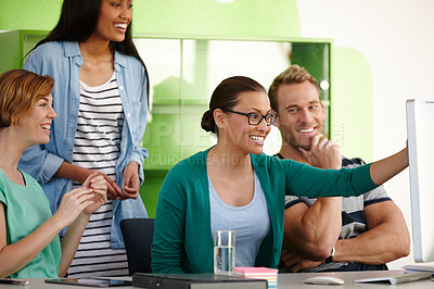 Buy stock photo Shot of a group of young designers working together at a computer