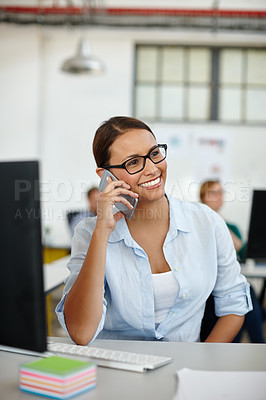 Buy stock photo Shot of a young female designer talking on the phone while sitting at her desk