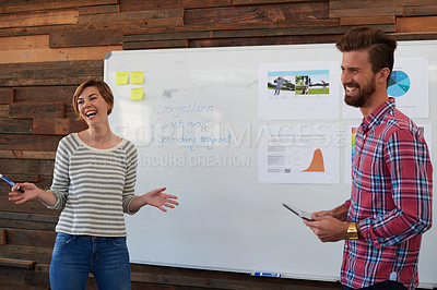 Buy stock photo Shot of two young designers brainstorming at a whiteboard