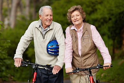 Buy stock photo Portrait of a happy mature couple walking with bicycle in countryside
