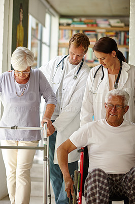 Buy stock photo Shot of a team of doctors assisting their senior patients with physical impairments