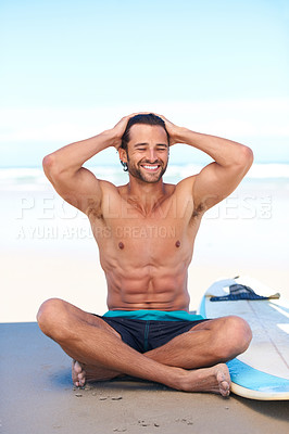 Buy stock photo An attractive young man on the beach slicking back his hair