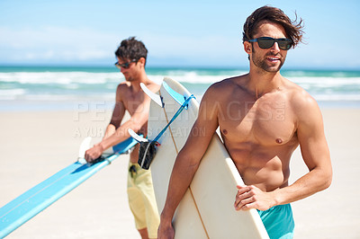 Buy stock photo Two friends at the beach getting ready to head into the water for a surf