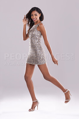 Buy stock photo Studio shot of a gorgeous  young woman posing in a sequined dress against a gray background