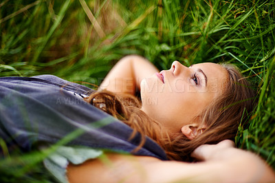 Buy stock photo Portrait of a beautiful woman lying in the grass