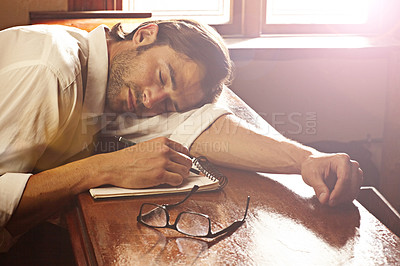 Buy stock photo A handsome young man sleeping on his notebook at a bar
