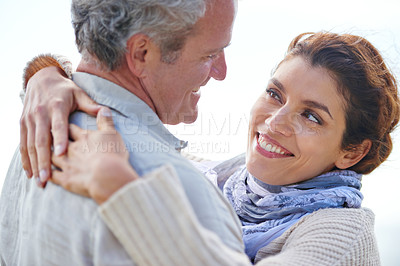 Buy stock photo Rearview shot of a mature man being hugged by his wife outdoors