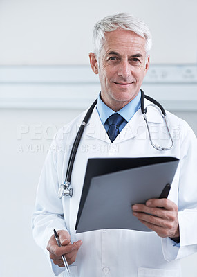 Buy stock photo Portrait of a confident mature doctor holding a medical chart