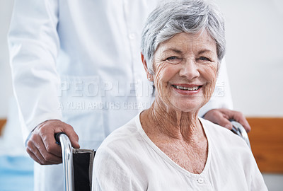Buy stock photo Shot of a senior woman in a wheelchair being pushed by a doctor