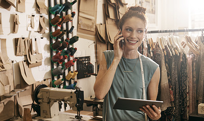 Buy stock photo Shot of a young dressmaker in her workshop doing business over the phone and online
