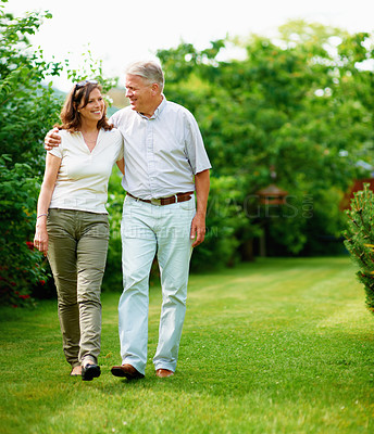 Buy stock photo Full length shot of a mature couple walking in their yard