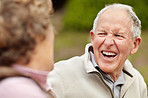 Cheerful mature man laughing while looking at senior woman