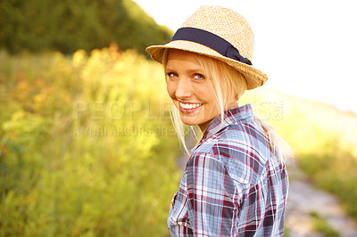 Buy stock photo Beautiful young woman in a field while wearing a straw fedora