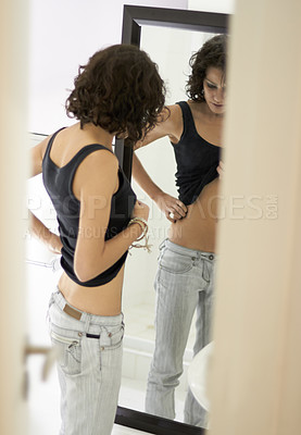 Buy stock photo A very skinny girl obsessing over her body