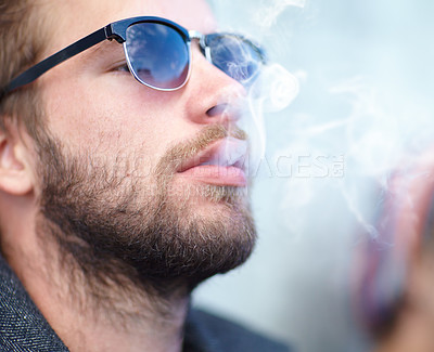 Buy stock photo Shot of a handsome man smoking hipster in sunglasses smoking